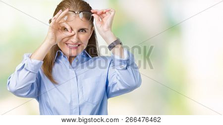 Beautiful middle age mature business woman wearing glasses over isolated background doing ok gesture with hand smiling, eye looking through fingers with happy face.