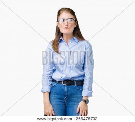Beautiful middle age mature business woman wearing glasses over isolated background making fish face with lips, crazy and comical gesture. Funny expression.