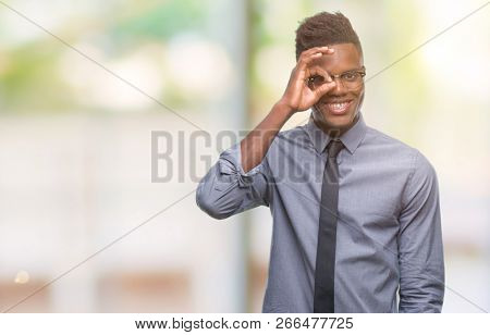 Young african american business man over isolated background doing ok gesture with hand smiling, eye looking through fingers with happy face.