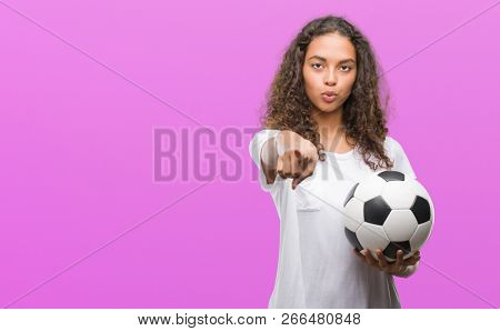 Young hispanic woman holding soccer football ball pointing with finger to the camera and to you, hand sign, positive and confident gesture from the front
