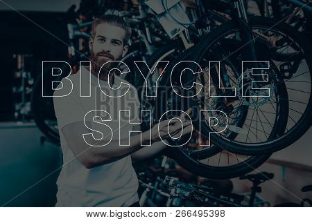 Bicycle Shop. Salesman Showing The Wheel Of Bicycle. Young Beard Man. Hipster Man Looking In To Came
