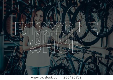 Bicycle Shop. Salesman Showing The Bicycles. Young Beautiful Woman. Woman Looking In To Camera. Woma
