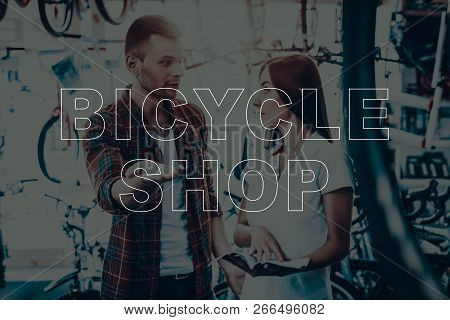 Bicycle Shop. Buyer Asks The Seller About The Bikes. Woman Looking On The Man. Woman Holding The Cat