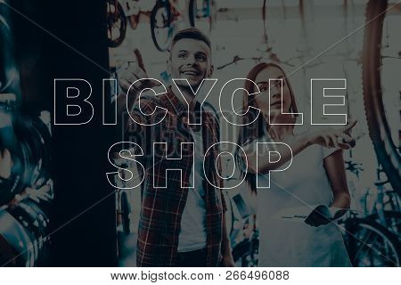 Bicycle Shop. Salesman Showing Bicycle To Customer. Man Pointing To Other Bike. Woman Holding The Ca