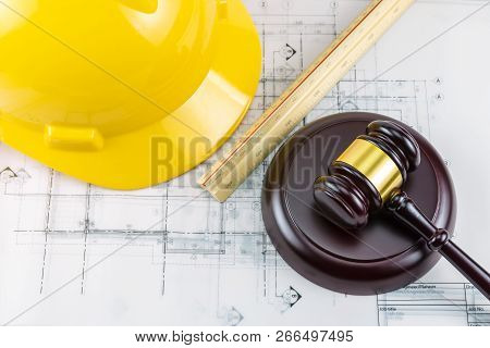 A Photo Of Gavel And Yellow Safety Helmet. This Photo Shot In Concept Idea Law About Construction De