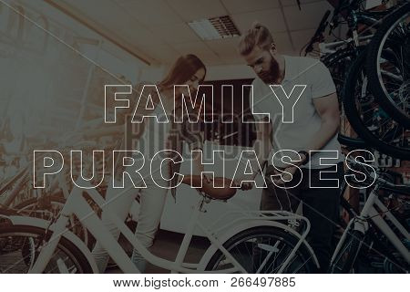 Family Purchases. Customer Choosing A Bicycle. Salesman Showing Back Of Bicycle To Customer. Custome