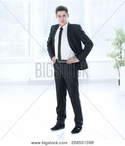 Full Growth.confident Young Businessman Standing In Office.