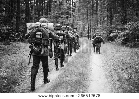 Re-enactors Dressed As German Infantry Soldiers In World War Ii Marching Walking Along Forest Road I