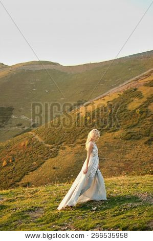 Bride In Vintage Wedding Dress Running Away At Sunset. Spectacular Mountain Landscape In The Backgro