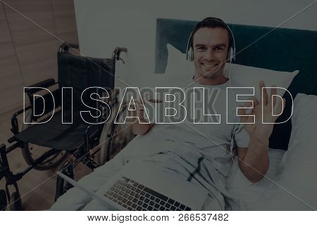 Disabled Man. Man Is Lying In Bed. Man Holding A Laptop. Man Wearing Headphones. Man Holding Cup Wit