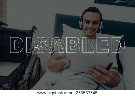 Disabled Man. Man Is Lying In Bed. Man Watching Video On Tablet Pc. Man Wearing Headphones. Man Is S