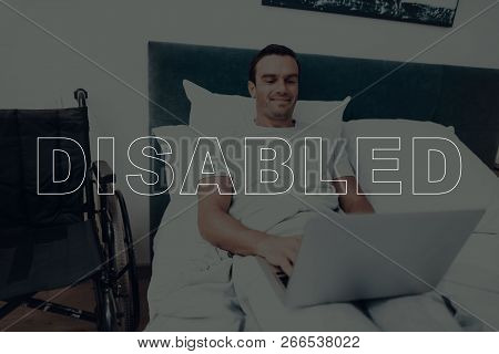 Disabled Man. Man Is Lying In Bed. Man Using A Laptop Computer. Man Typing On Laptop. Man Is Smiling