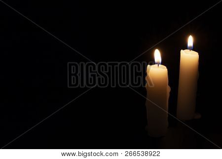 Two Candles On Black Background. Lighting Candles In Darkness. Yellow Wax Candle With Warm Flame. In