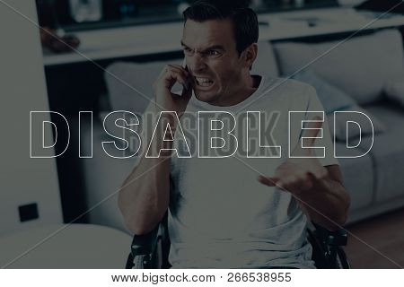 Disabled Man In A Wheelchair. Man Talking On Mobile Phone. Man Have Call On Smartphone. Man Is Angry