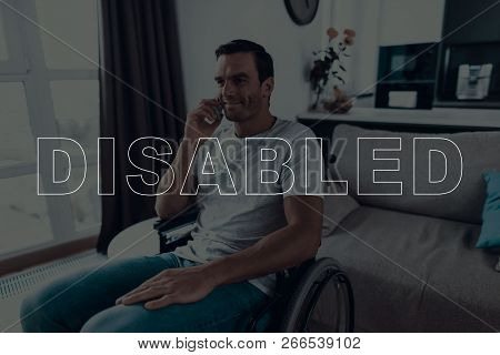 Disabled Man In A Wheelchair. Man Sits In Front Of Window. Man Talking On Mobile Phone. Man Have Cal