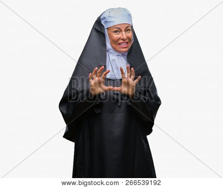 Middle age senior christian catholic nun woman over isolated background disgusted expression, displeased and fearful doing disgust face because aversion reaction. With hands raised. Annoying concept.