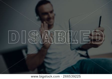 Disabled Man In A Wheelchair. Man Have A Video Call. Video Call On Tablet Pc. Man Wearing A Headphon