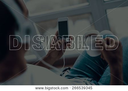 Disabled Man In A Wheelchair. Man Sits In Front Of Window. Man Using Mobile Phone. Man Listening Mus