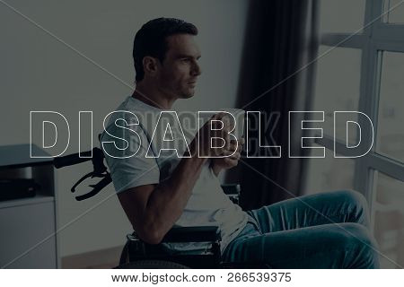 Disabled Man In A Wheelchair. Man Sits In Front Of Window. Large Panoramic Window. Man Looks Into Wi