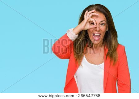 Beautiful middle age business adult woman over isolated background doing ok gesture with hand smiling, eye looking through fingers with happy face.