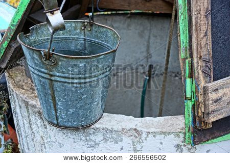 Gray Metal Bucket Of Water Standing On An Open Well In The Street