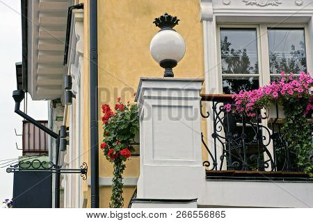 White Round Lantern On The Wall By The Balcony With Flowerpots And A Window