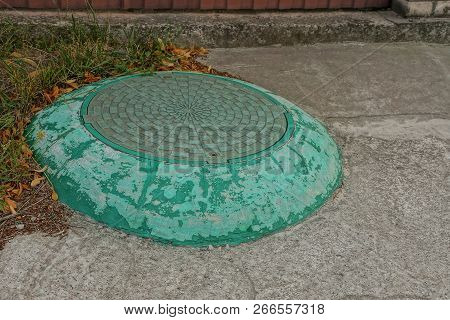 Green Iron Manhole In Concrete On Asphalt Road And In The Grass
