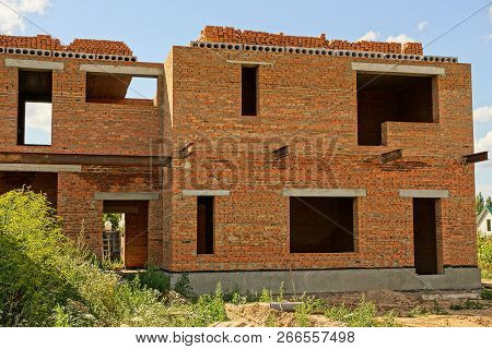Large Unfinished Brown Brick House In Green Grass