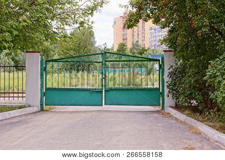 Green Iron Gate And Fence In Green Vegetation On An Asphalt Road