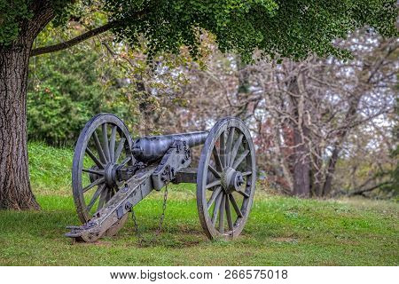A Long Silent Civil War Cannon Sits In A Virginia Field.
