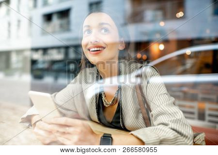 View Through The Window On The Stylish Woman Sitting With Phone Indoors With Modern Building On The