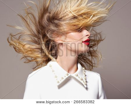 beauty portrait of attractive ypung caucasian womanblond on beije background studio shot hair wind blowing red lips