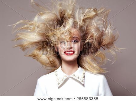 beauty portrait  attractive young caucasian woman blond on beije background studio shot hair wind blowing red lips looking at camera smiling toothy smile happy cheerful