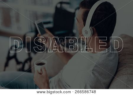 Disabled Man. Man Is Sitting On Sofa. Wheelchair On Background Of Man. Man Wearing A Headphones. Man