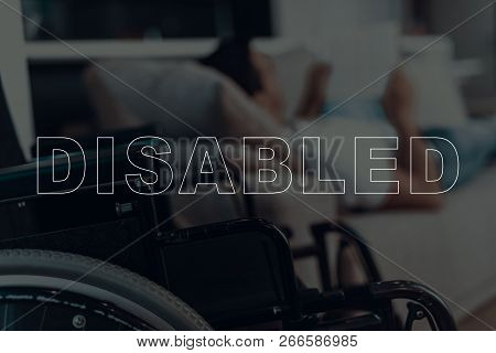 Disabled Man. Man Lying On Sofa. Wheelchair On Background Of Man. Man Reading Something. Reading On