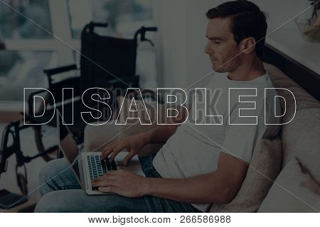 Disabled Man. Man Is Sitting On Sofa. Wheelchair On Background Of Man. Man Using A Laptop. Man Is Ty