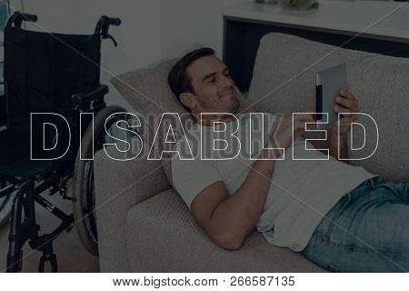 Disabled Man. Man Lying On Sofa. Wheelchair On Background Of Man. Man Using A Tablet Pc. Man Typing