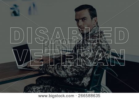 Military Veteran. Disabled Man In A Wheelchair. Man Sitting At Table. Man Using Laptop. Man Is Soldi