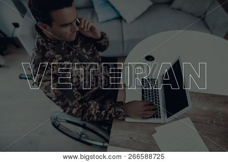 Military Veteran. Disabled Man In A Wheelchair. Man Sitting At Table. Man Using S Laptop. Man Is Sol
