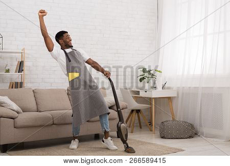 Yeah, I Did It. Excited African-american Man Celebrating Achievement While Cleaning House With Wirel