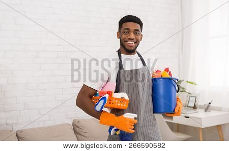 Cleaning Products. Cheerful African-american Guy Cleaner Holding Lots Of Detergents, Ready For House