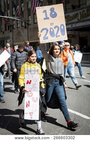 March For Our Lives: A young woman marches holding a sign that says 18 By 2010 during the march to end gun violence on 6th Ave, NEW YORK MAR 24 2018.