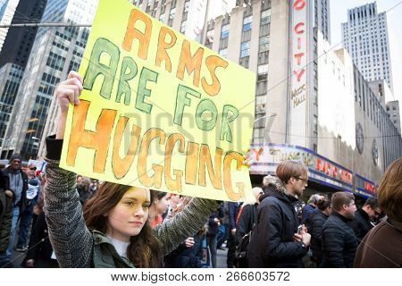 March For Our Lives: A young woman marching holds a sign that says Arms Are For Hugging during the march to end gun violence on 6th Ave, NEW YORK MAR 24 2018.