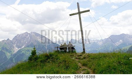 At The Summit Cross, Two Hikers Enjoy The View Of The Lechtal Alps In Tyrol In Austria