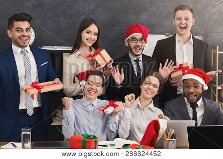 Happy Business Team Enjoying Christmas Party In Office, Holding Gift Boxes After Secret Santa Game,