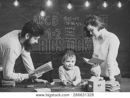Father And Mother Reading Books, Teaching Their Son, Chalkboard On Background. Family Cares About Ed