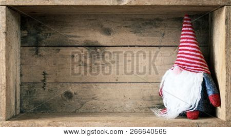 A Christmas decoration with a gnome in a wooden box background