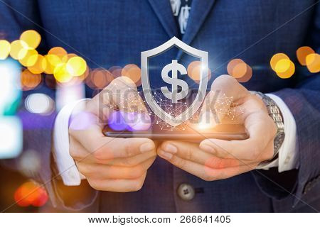 The Concept Is The E-money Security. A Businessman Is Holding A Mobile Phone With The Hanging Above