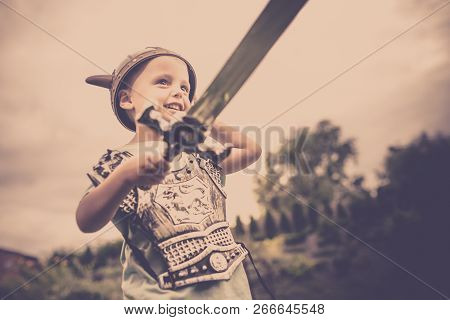 Cute little Caucasian boy holding a sword pretending to be a fearless knight poster