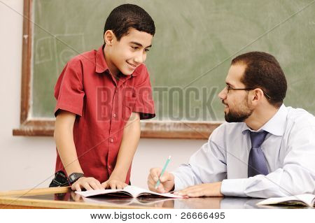 Teacher helping pupil in classroom to resolve schoolwork poster